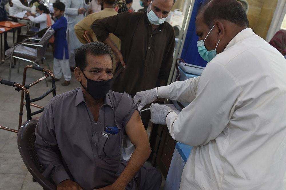 A health worker inoculates a man with a dose of AstraZeneca-Oxford's Covid-19 vaccine at a vaccination centre in Karachi on May 10. — AFP/File