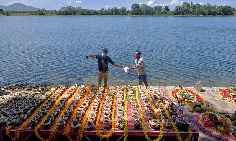 Municipal workers gestures next to over 560 unclaimed clay urns containing ashes of people who died due to Covid-19 coronavirus on the banks of river Cauvery before a mass immersion ritual organised by the government of Karnataka, in Belakavadi Village in Mandya District situated about 125 Km from Bangalore on June 2, 2021. (Photo by Manjunath Kiran / AFP)