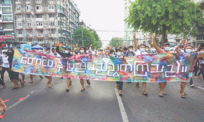 YANGON: Protesters hold aloft a banner that reads 'Hills and the Central Region are united' as they give the  three-finger salute during a demonstration against the military coup on Thursday.—AFP