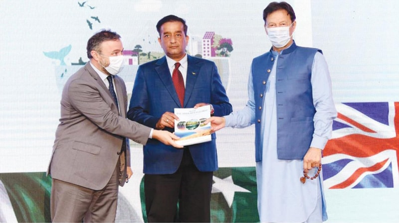 Prime Minister Imran Khan being presented a copy of the First Blue Carbon Assessment Study on Thursday.—PPI