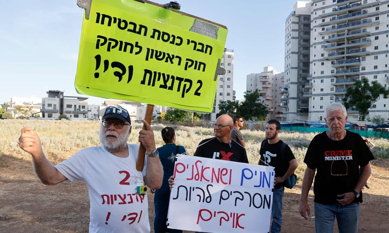 """Supporters of Israeli """"change coalition"""" shout slogans and wave the national flag during a demonstration in support of the coalition to form a government, in the central Israeli city Petah Tikva, on June 3. — AFP"""