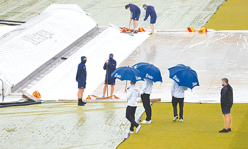 LONDON: The umpires inspect the pitch as groundstaff clear water off a cover after rain disrupted play on the third day of the first Test between England and New Zealand at Lord's on Friday. — AFP
