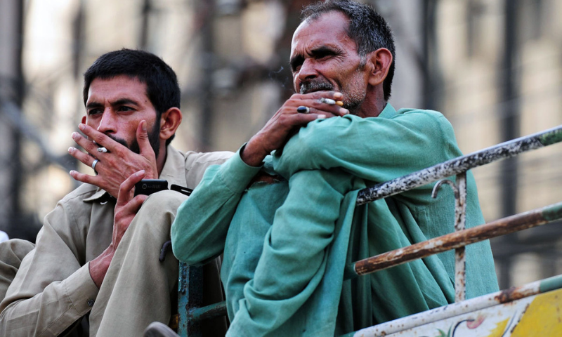 Pakistani residents smoke cigarettes as they ride a passenger bus in Karachi. — AFP/File