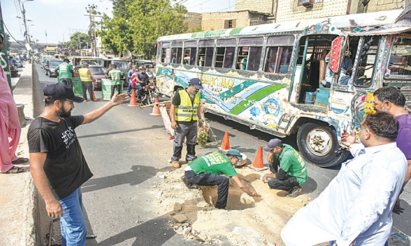 Volunteers replace a manhole cover on Jahangir Road.—Fahim Siddiqi/White Star