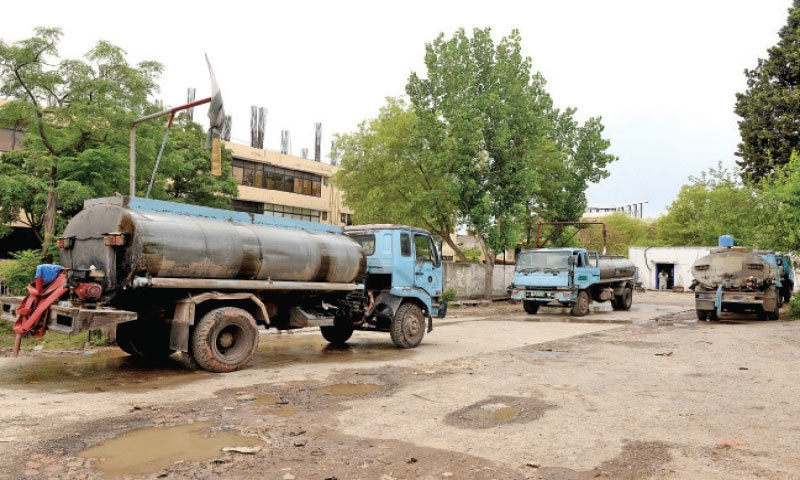 Tankers are seen parked at the CDA's G-10 office where they are filled with water to supply to residents of sectors facing shortage of the commodity. The other picture shows people filling their cans with water from a tubewell in a locality in Islamabad. — Photos by Mohammad Asim