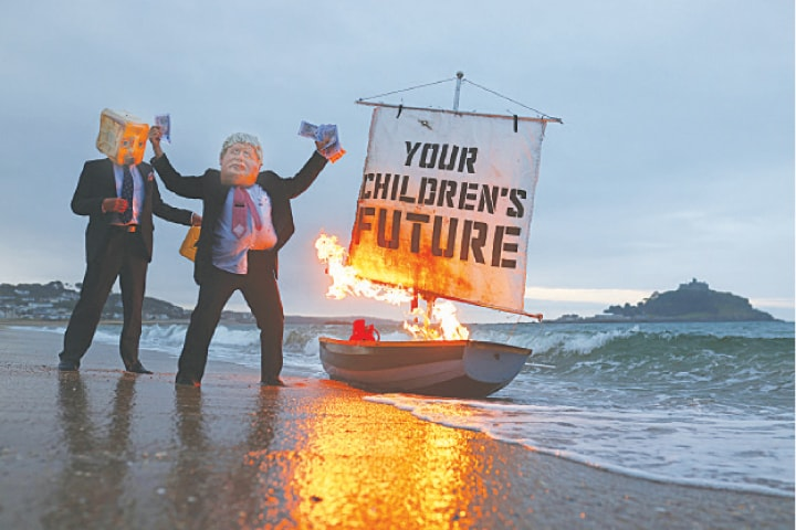 Activists from climate action group Ocean Rebellion set a boat on fire during a demonstration at sunrise at Marazion Beach in Cornwall ahead of the G7 summit in Carbis Bay on Saturday.—Reuters