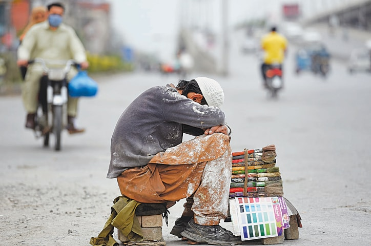 A painter sits idly by the side of a road in Rawalpindi, waiting for customers | Tanveer Shahzad/White Star