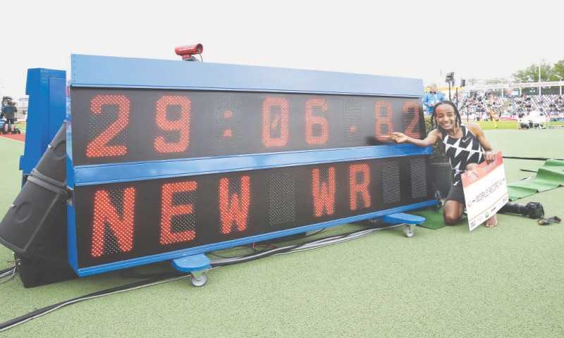 DUTCH athlete Sifan Hassan poses with scoreboard after setting a new world record on Sunday.—AFP