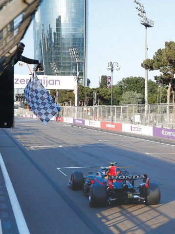 BAKU: The checkered flag waves for Red Bull's Sergio Perez of Mexico as he crosses the finish line to win the F1 Grand Prix at the Baku Formula One city circuit on Sunday.—Reuters