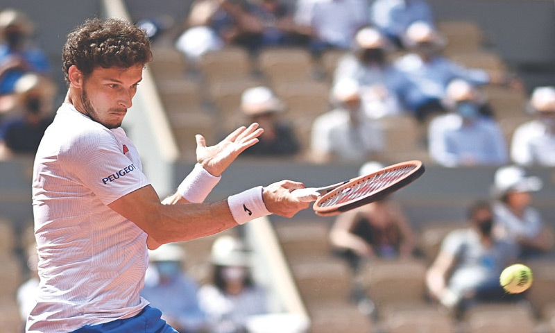PABLO Carreno Busta of Spain returns the ball to Greece's Stefanos Tsitsipas during their men's singles fourth-round match at the Roland Garros on Sunday.—AFP