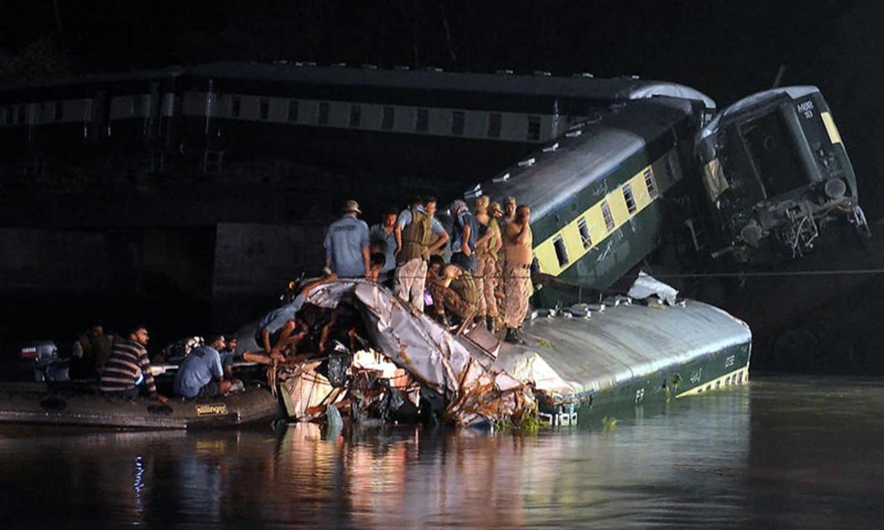 Pakistani rescue workers and troops inspect the wreckage of a train carrying soldiers and military hardware after it fell into a canal following the partial collapse of a bridge in Wazirabad, Gujranwala, July 2, 2015. — AFP/File