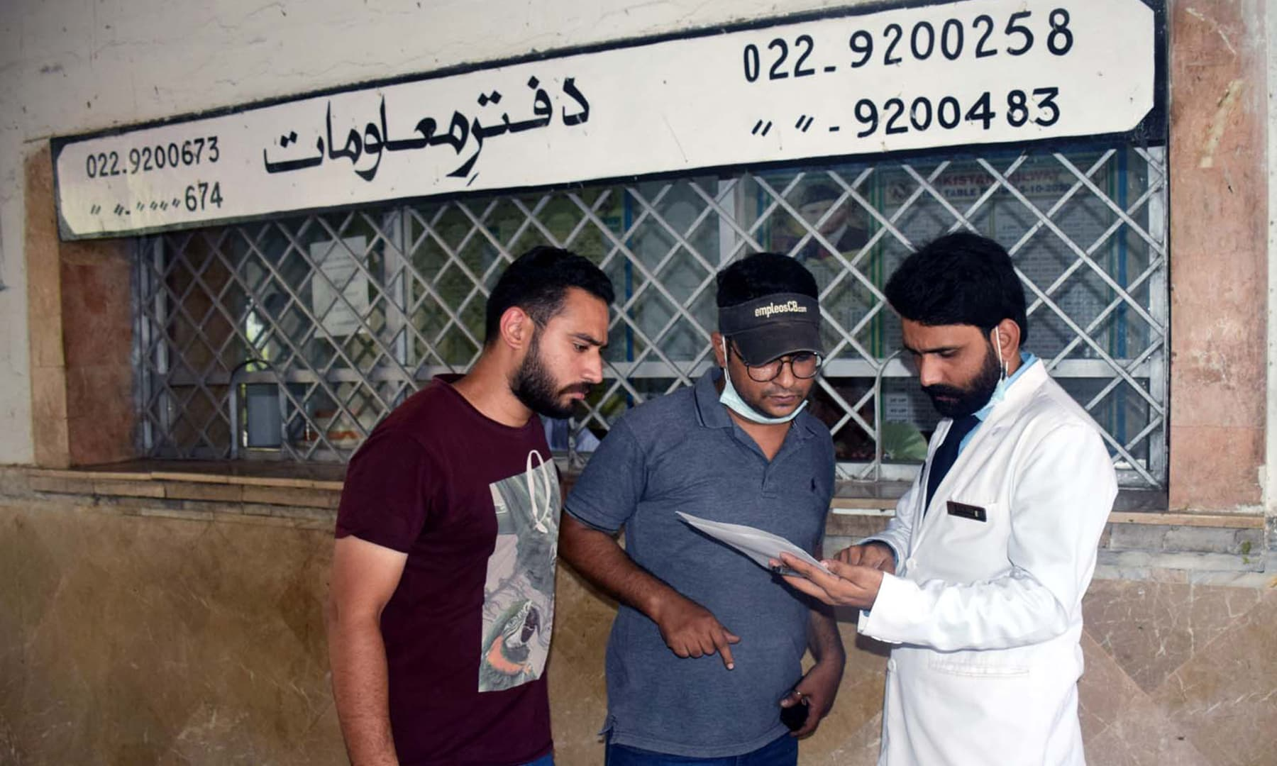 A man verifies the name of his brother-in-law in the list of passengers who boarded the Millat Express from Hyderabad. — Umair Ali