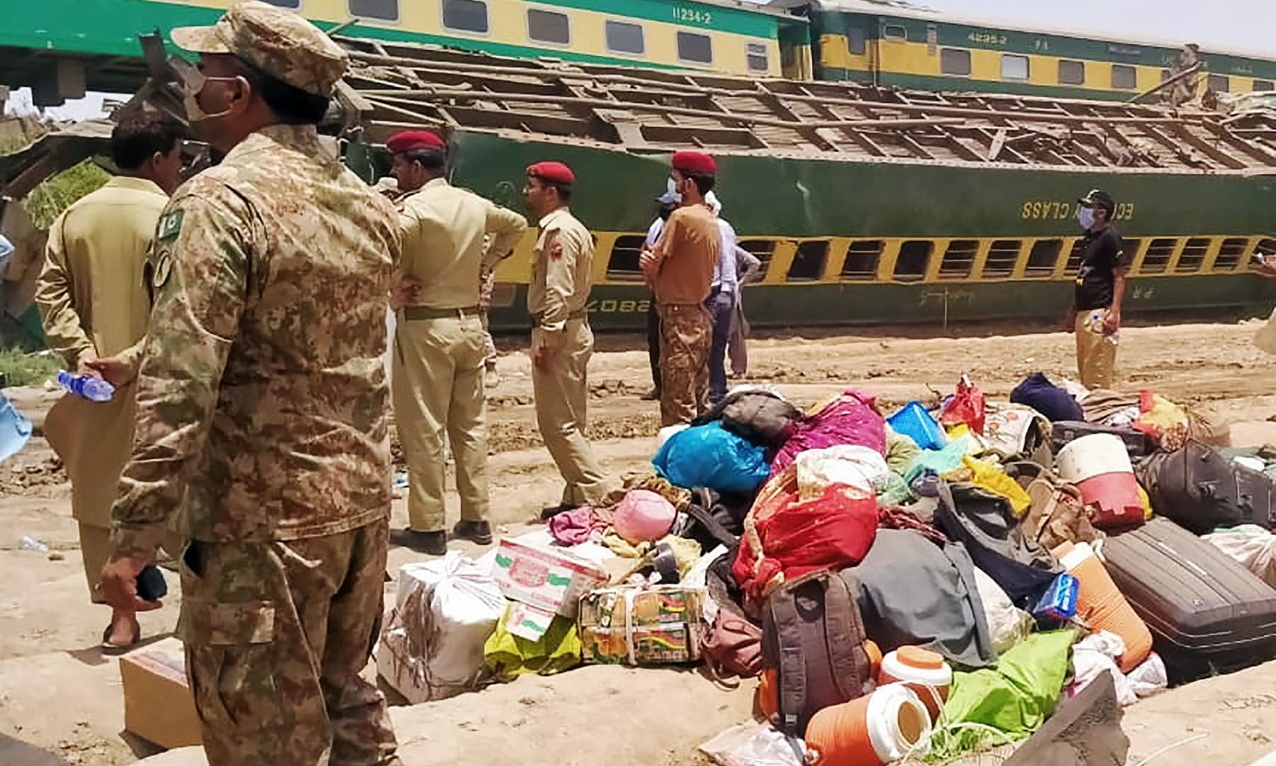 Security personnel stand at the site of a train accident in Daharki area of northern Sindh on June 7. — AFP