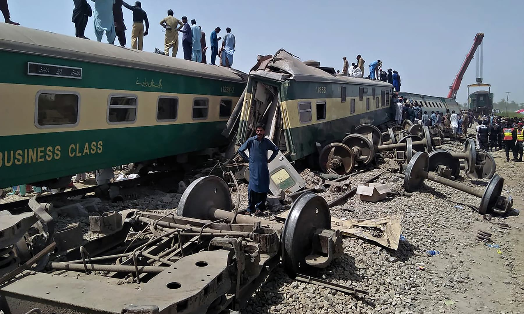Soldiers and volunteers work at the site of a train collision in Ghotki, Monday, June 7. — AP