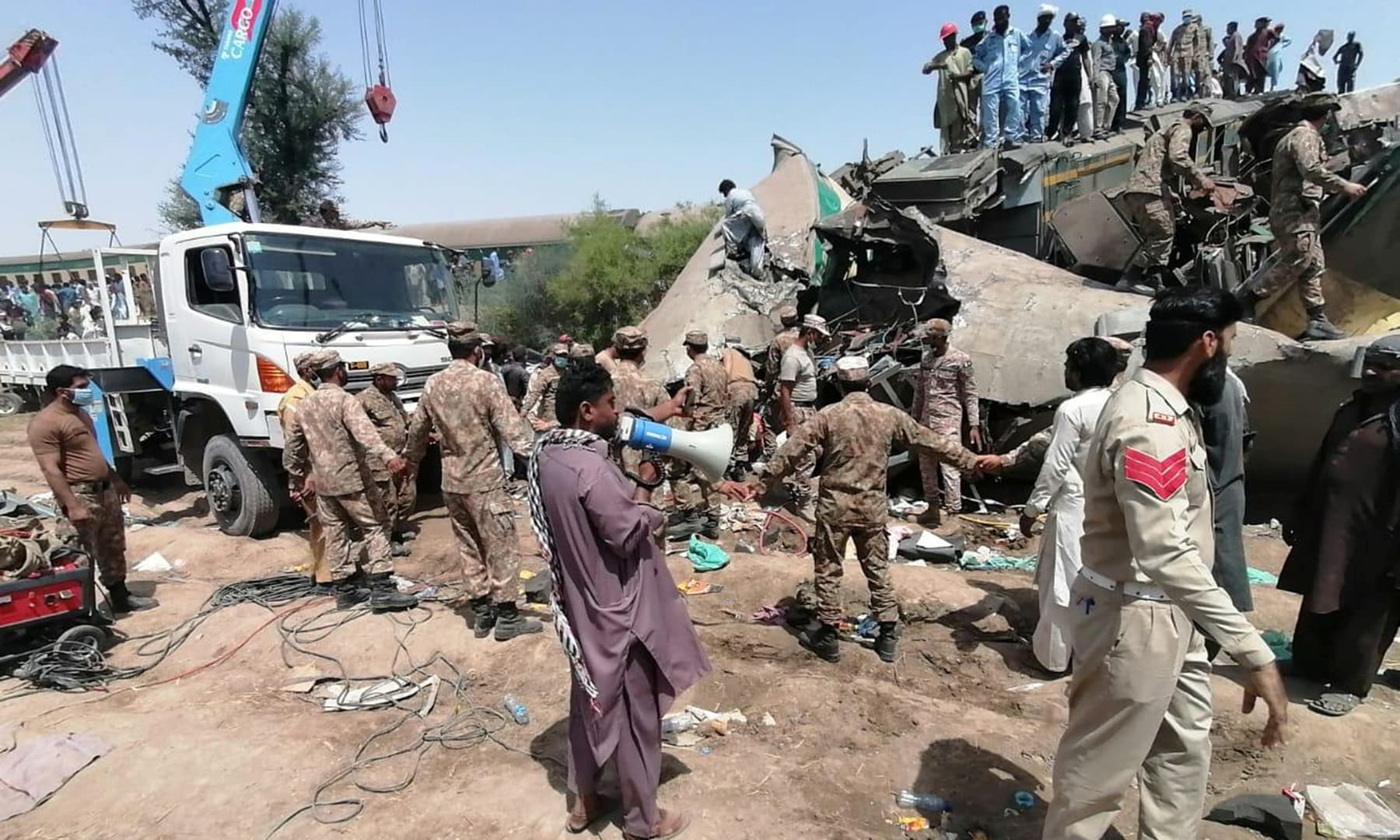 Paramilitary soldiers and rescue workers gather at the site of a collision between two trains in Ghotki, June 7. — ISPR via Reuters