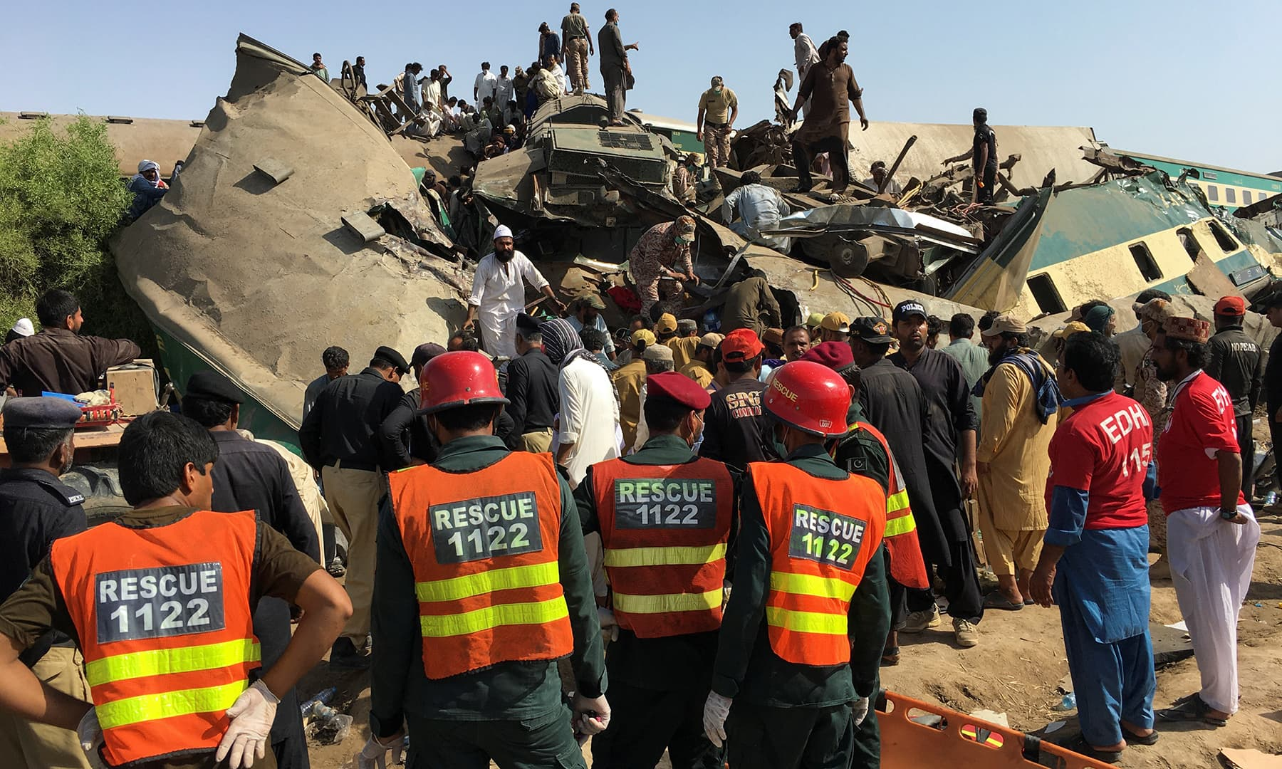 Rescue workers stand as people gather at the site of a collision between two trains in Ghotki, June 7. — Reuters