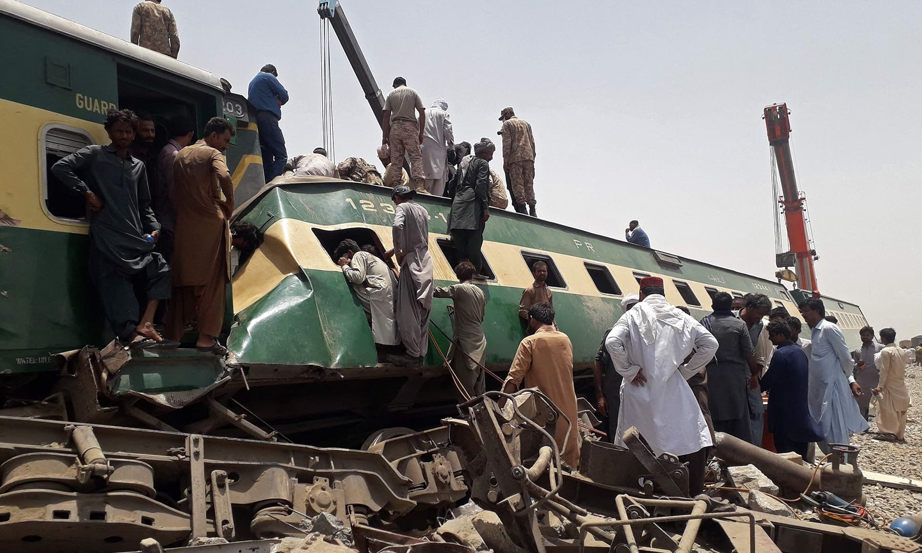 Security personnel and onlookers stand at the site of a train accident in Daharki on June 7. — AFP