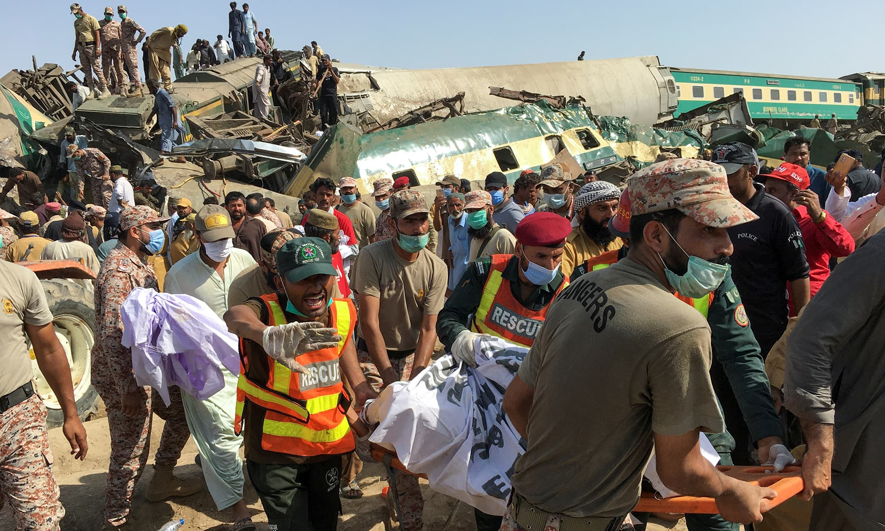 Paramilitary soldiers and rescue workers move the body of a man from the site of a collision between two trains in Ghotki, June 7. — Reuters