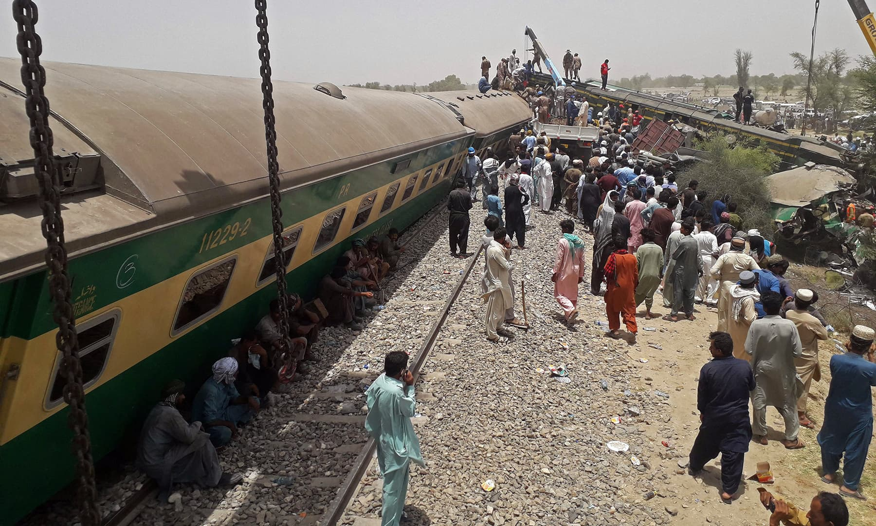 Security personnel and onlookers stand at the site of a train accident in Daharki area of northern Sindh on Monday. — AFP