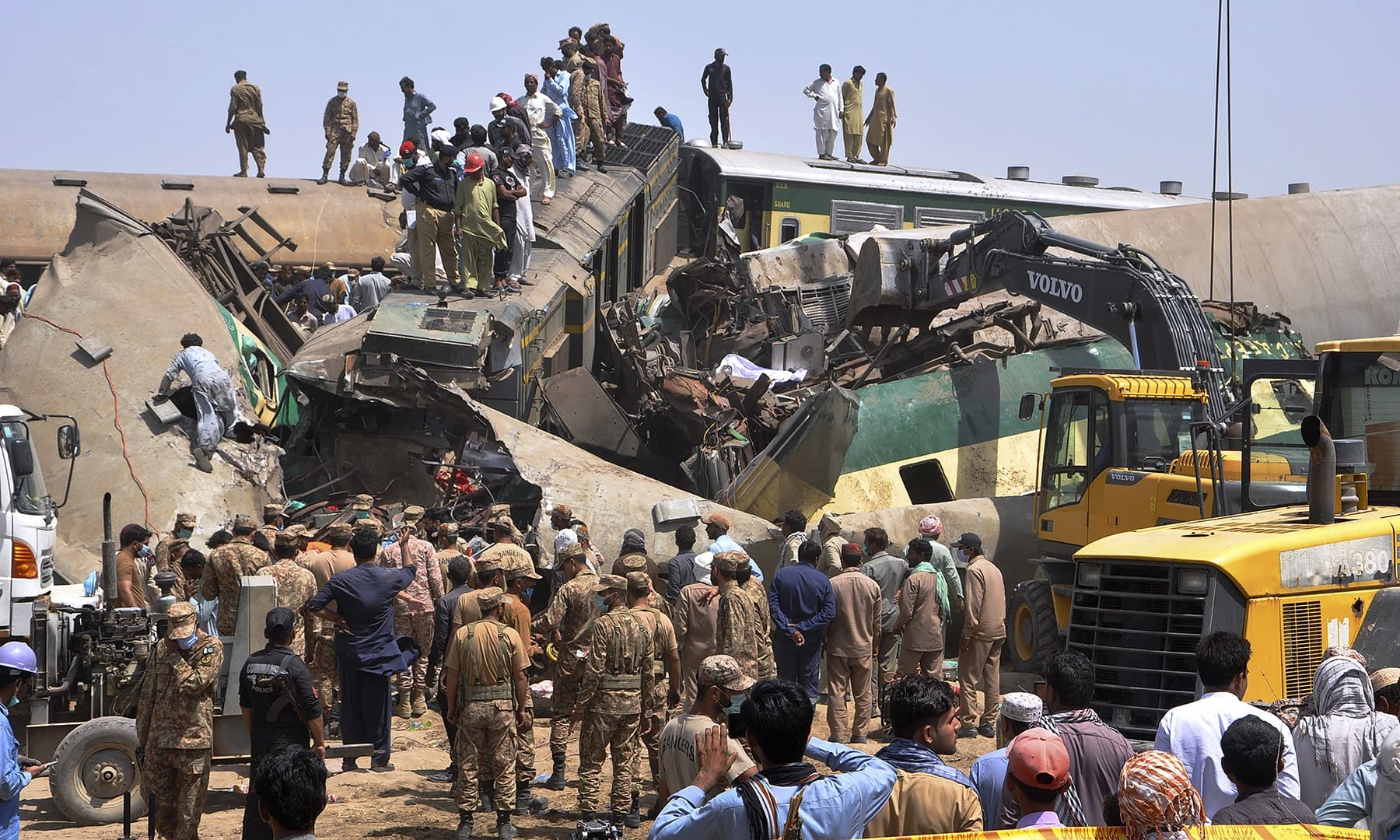 Soldiers and volunteers work at the site of a train collision in the Ghotki district in southern Pakistan, Monday, June 7, 2021. Two express trains collided in southern Pakistan early Monday, killing dozens of passengers, authorities said, as rescuers and villagers worked to pull injured people and more bodies from the wreckage. (AP Photo/Waleed Saddique) — Copyright 2021 The Associated Press. All rights reserved.
