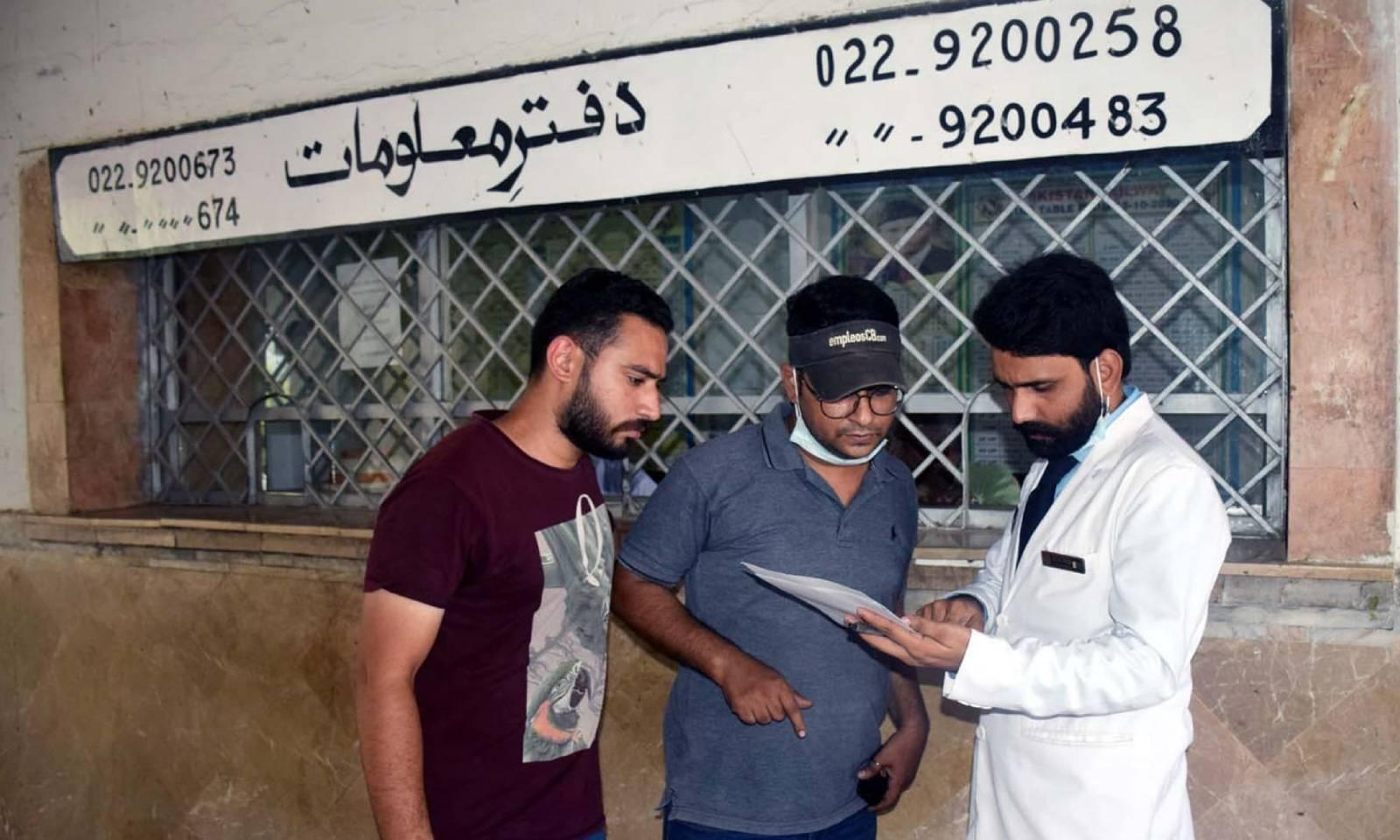 ایک شخص  حیدرآباد سے ملت  ایکسپریس میں سوار اپنے ایک عزیز کے نام کی تصدیق کررہا ہے — فوٹو: عمیر علی