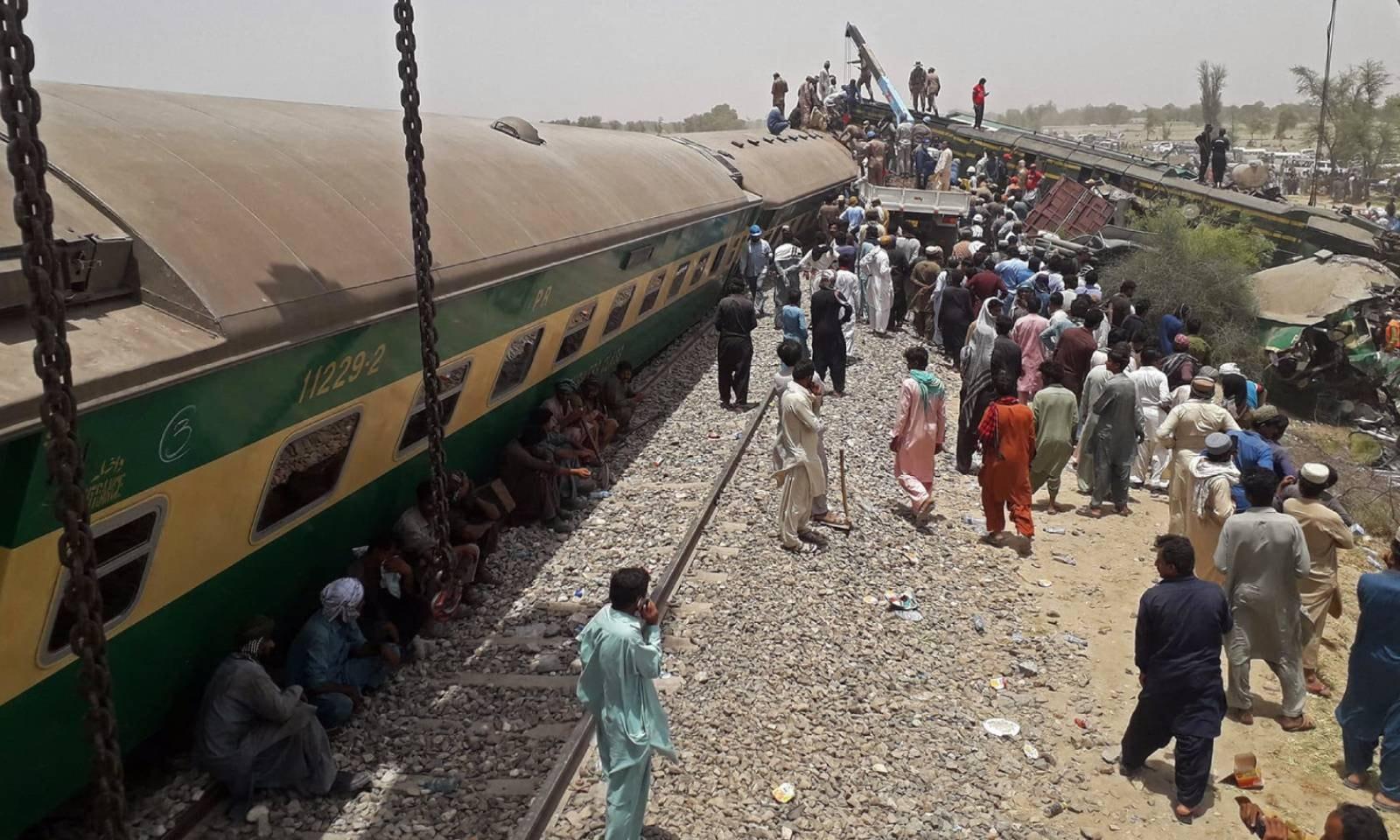 حادثہ رات ساڑھے تین بجے اس وقت پیش آیا جب ملت ایکسپریس ٹرین کی 10 سے زائد بوگیاں پٹڑی سے اتر گئی تھیں اور مخالف سمت سے آنے والی سرسید ایکسپریس ان سے ٹکرائی—فوٹو: اے ایف پی