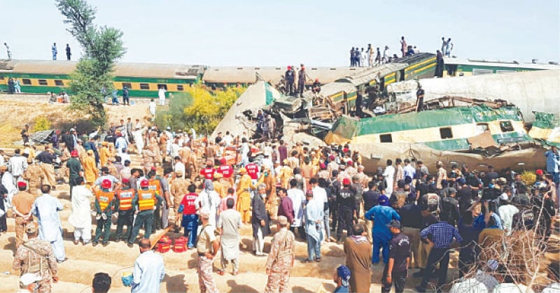 ARMY officials and rescue workers gather at the site of the train tragedy on Monday.—PPI