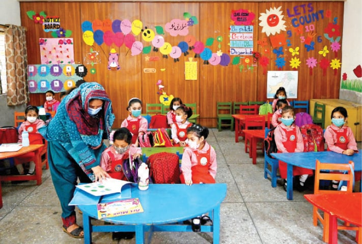 A teacher attends to a student in a class at the Islamabad Model College for Girls, I-8/4, on Monday. Educational institutions reopened in cities that have recorded a positivity ratio below 5pc. — Photo by Mohammad Asim