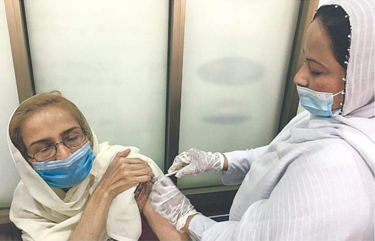 QUETTA: A health worker administers anti-Covid vaccine to a woman on Monday.—PPI
