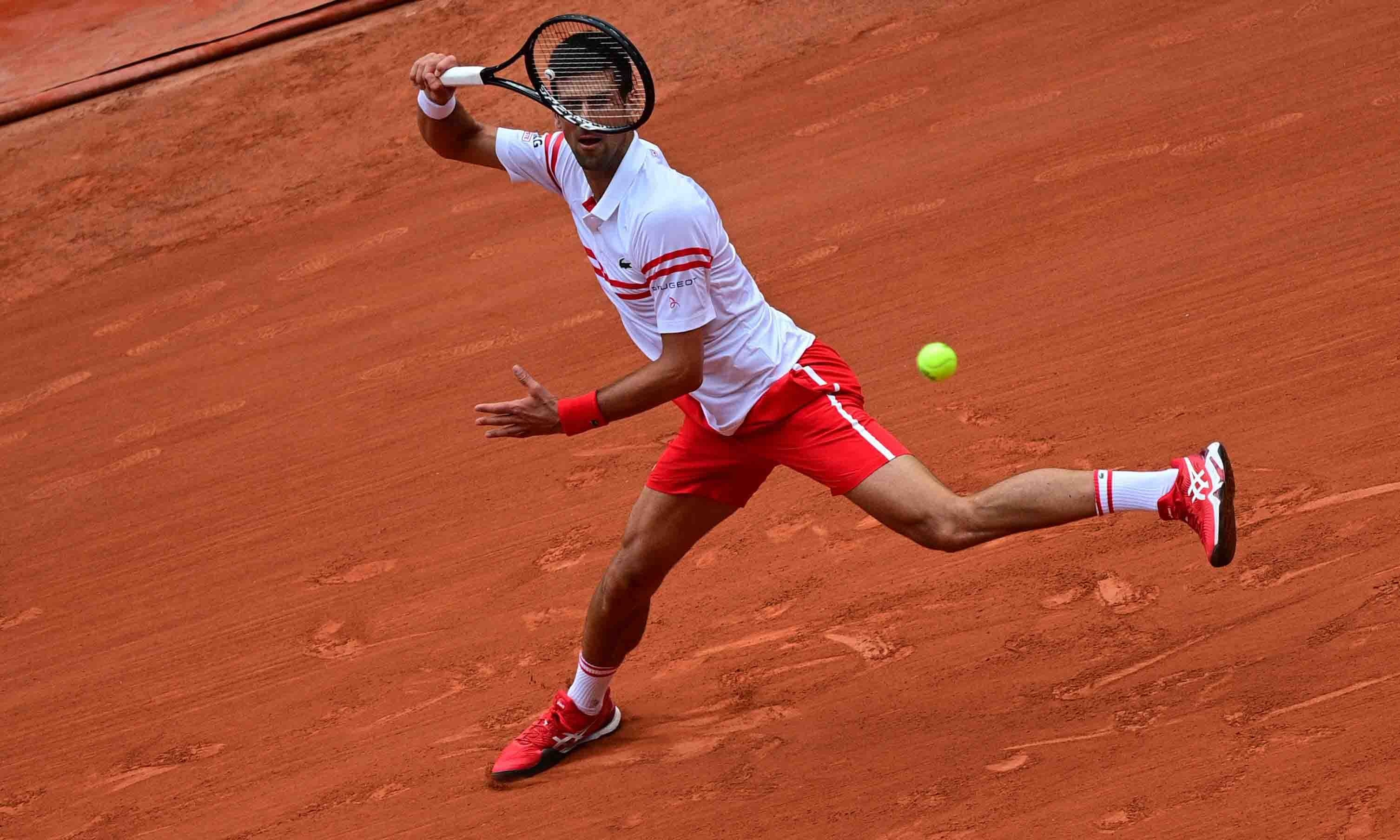 Serbia's Novak Djokovic returns the ball to Italy's Lorenzo Musetti during their men's singles fourth round tennis match on Day 9 of The Roland Garros 2021 French Open tennis tournament in Paris on June 7. — AFP