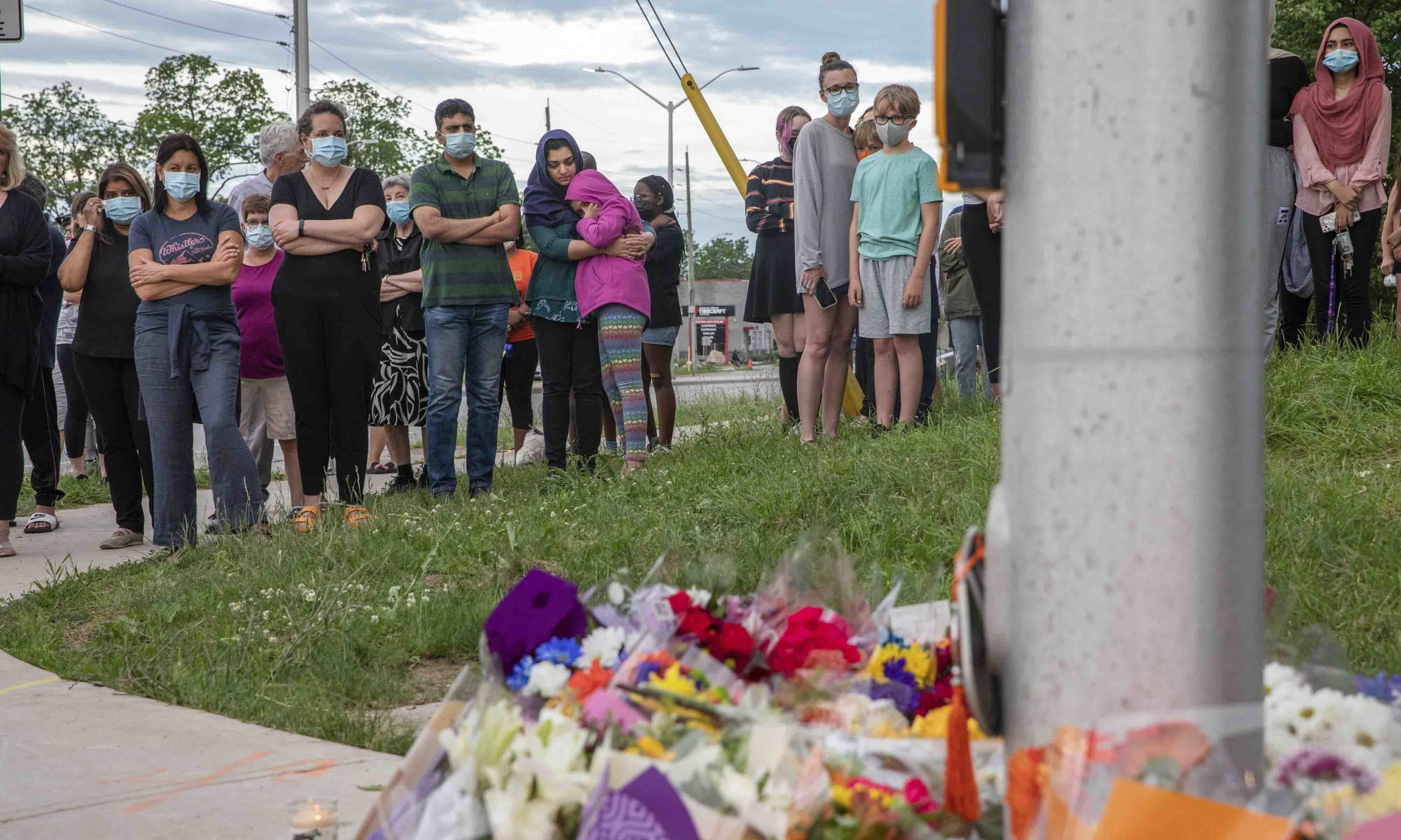 People attend a memorial at the location where a family of five was hit by a driver, in London, Ontario, on June 7. — AP