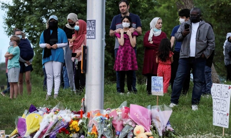 People gather at a makeshift memorial at the fatal crime scene where a man driving a pickup truck jumped the curb and ran over a Muslim family. — Reuters