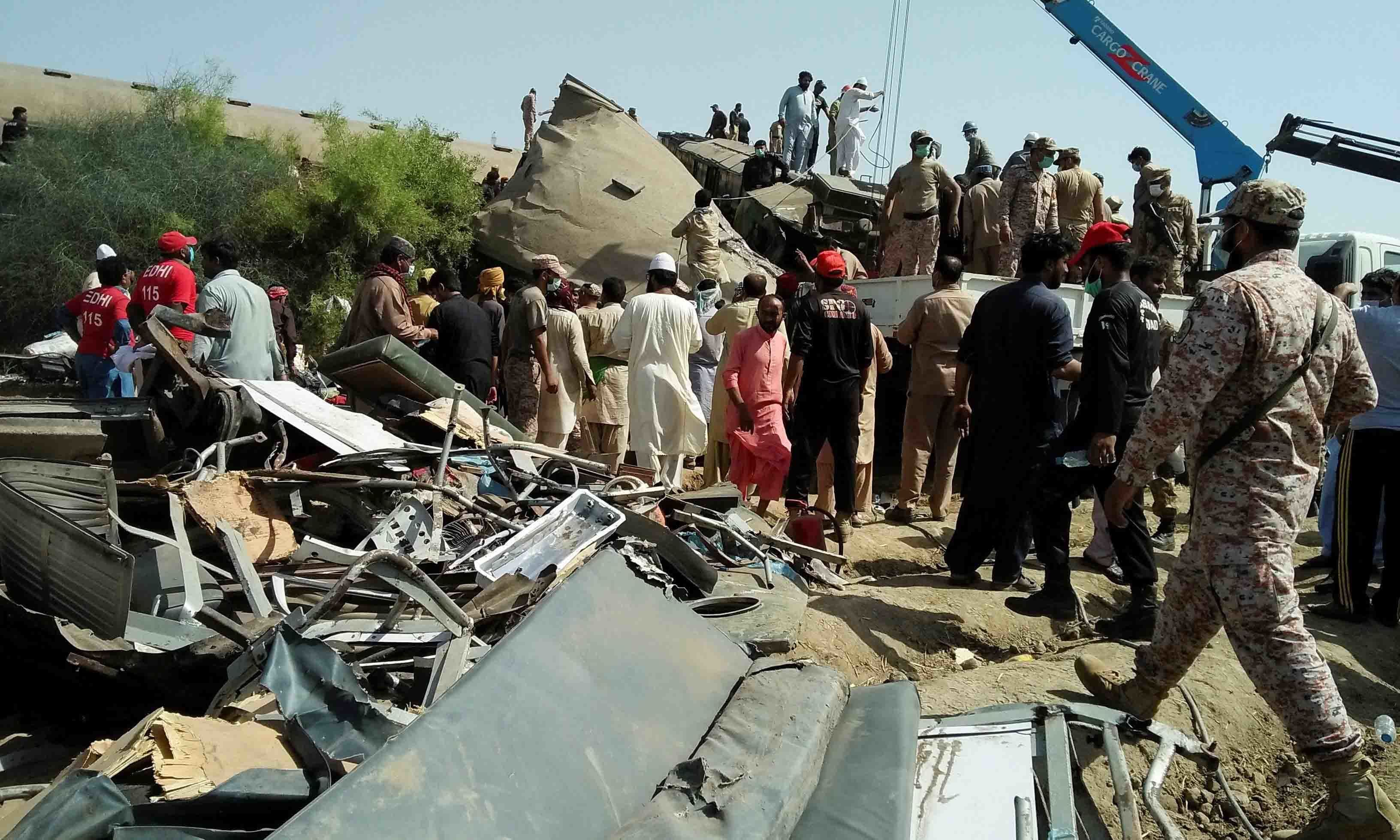 Paramilitary soldiers and rescue workers gather at the site following a collision between two trains in Ghotki, Pakistan June 7. — Reuters