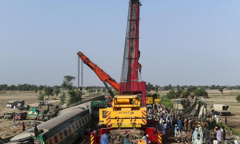 Railway labourers work to clean the wreckage from a railroad track in Daharki on June 8, 2021, a day after a packed intercity train ploughed into another express that had derailed. — AFP /File