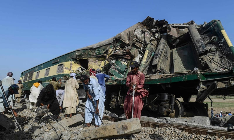 Railway workers try to fix a track beside wreckage of a carriage in Daharki on June 8, 2021, a day after a packed intercity train ploughed into another express that had derailed. — AFP