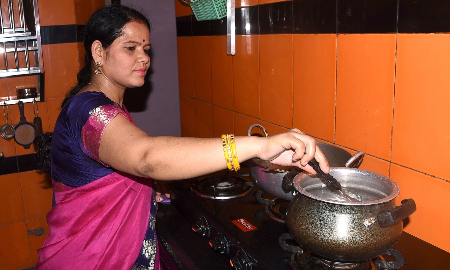 In this picture taken on June 4, 2021 Tanya Ashnigdh, who is in her fourth month of pregnancy, cooks at her home in Muzaffarpur city in the eastern state of Bihar. Ashnigdh is frightened, one of millions of expectant mothers excluded from India's faltering vaccination drive despite being at greater risk from Covid-19. — AFP