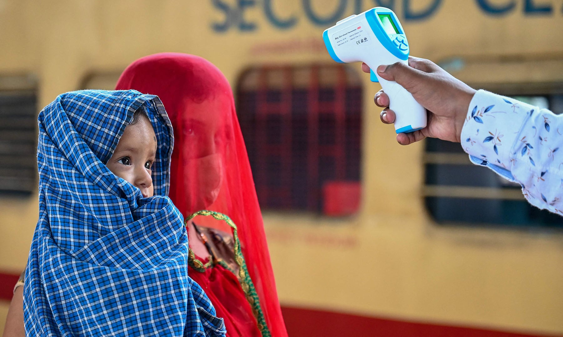 A health worker checks the body temperature of a passenger during a Covid-19 screening as she arrives with her child at a railway platform on a long distance train, in Mumbai on June 8, 2021. — AFP