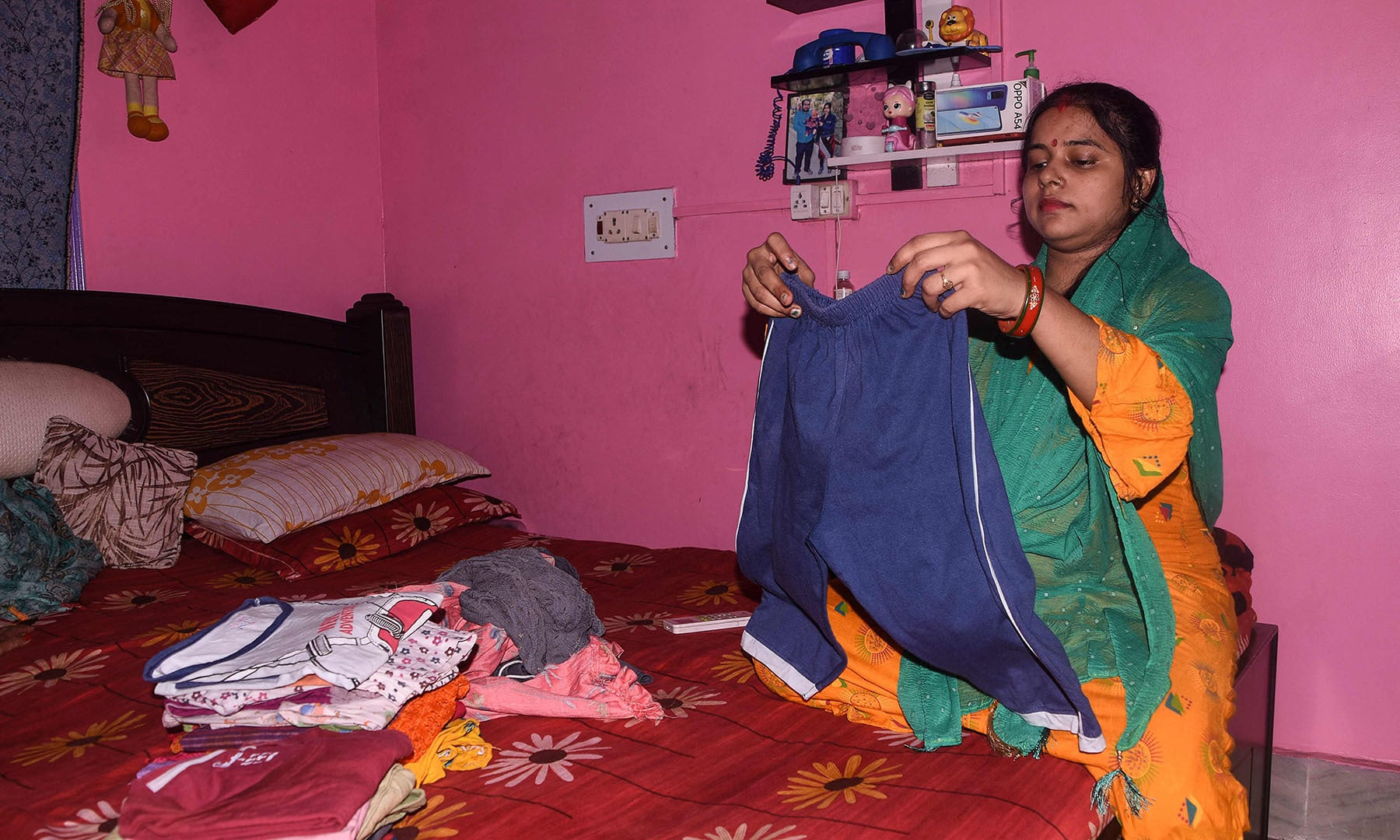 In this picture taken on June 4, 2021 Kumari Kajal, who is in her eighth month of pregnancy, folds clothes at her home in Muzaffarpur city in the eastern state of Bihar. — AFP