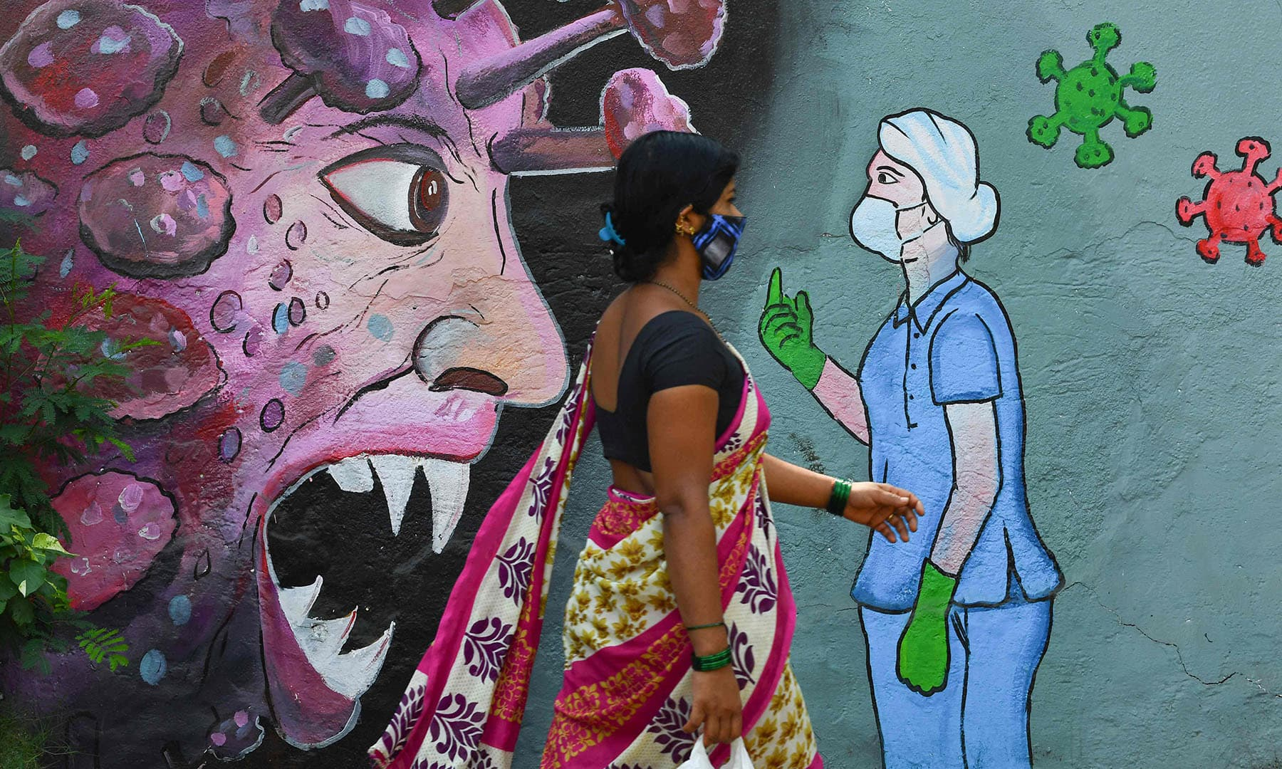 A pedestrian walks past a wall mural depicting a frontline medical staff stopping the Covid-19 coronavirus, in Navi Mumbai on June 7, 2021. — AFP