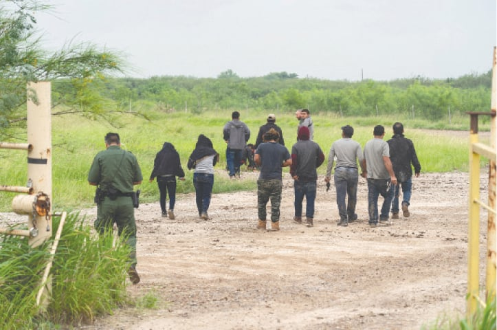 LA JOYA (Texas, US): Migrants from Central American countries are being arrested by US security personnel on Tuesday after they crossed the Rio Grande river from Mexico.—Reuters