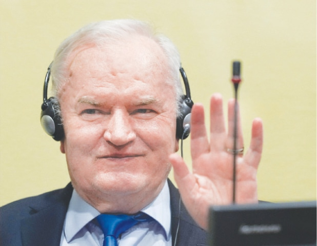 Bosnian Serb military leader Ratko Mladic waves in the courtroom before the ruling.—Reuters