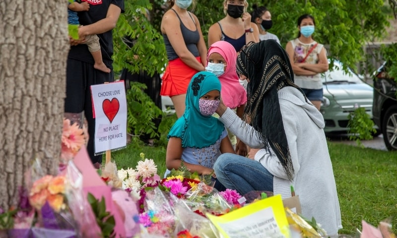 Kira Stephani speaks with her daughters Aisha Sayyed (front) and Aliyah Sayyed at a makeshift memorial at the fatal crime scene where a man driving a pickup truck jumped the curb and ran over a Muslim family in London, Ontario. — Reuters