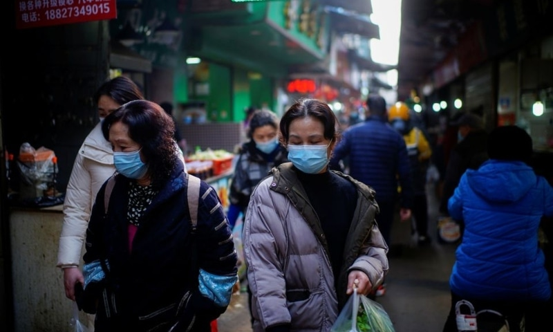 People wearing face masks walk on a street market, following an outbreak of the coronavirus disease in Wuhan, Hubei province, China February 8. — Reuters