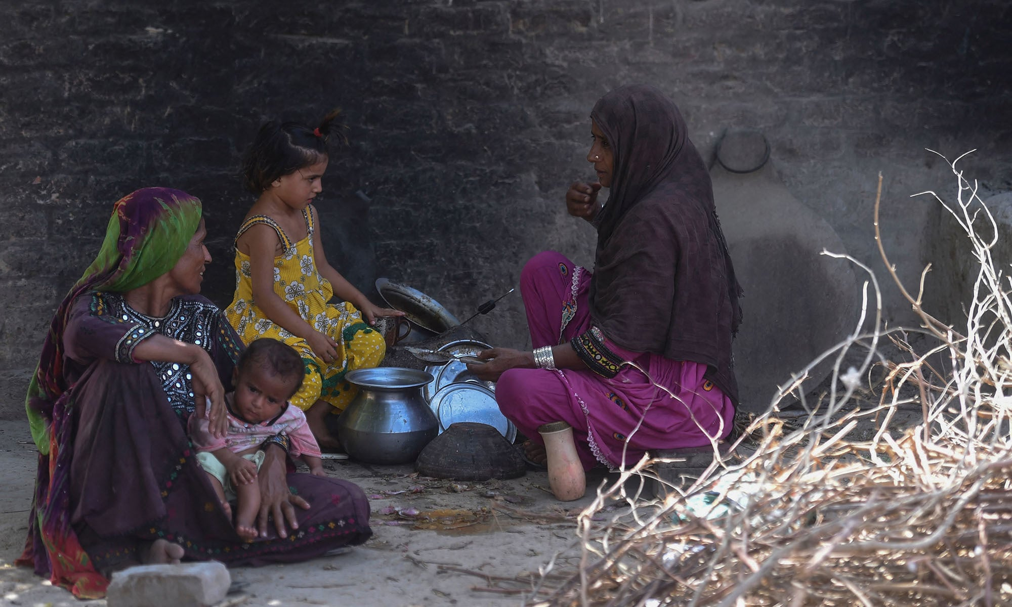 Habiba Mai (R), wife of school teacher Ali Nawaz, who helped with the rescue efforts of the train collision, prepares tea for her family at her home near the train accident site in Daharki, Sindh. —AFP