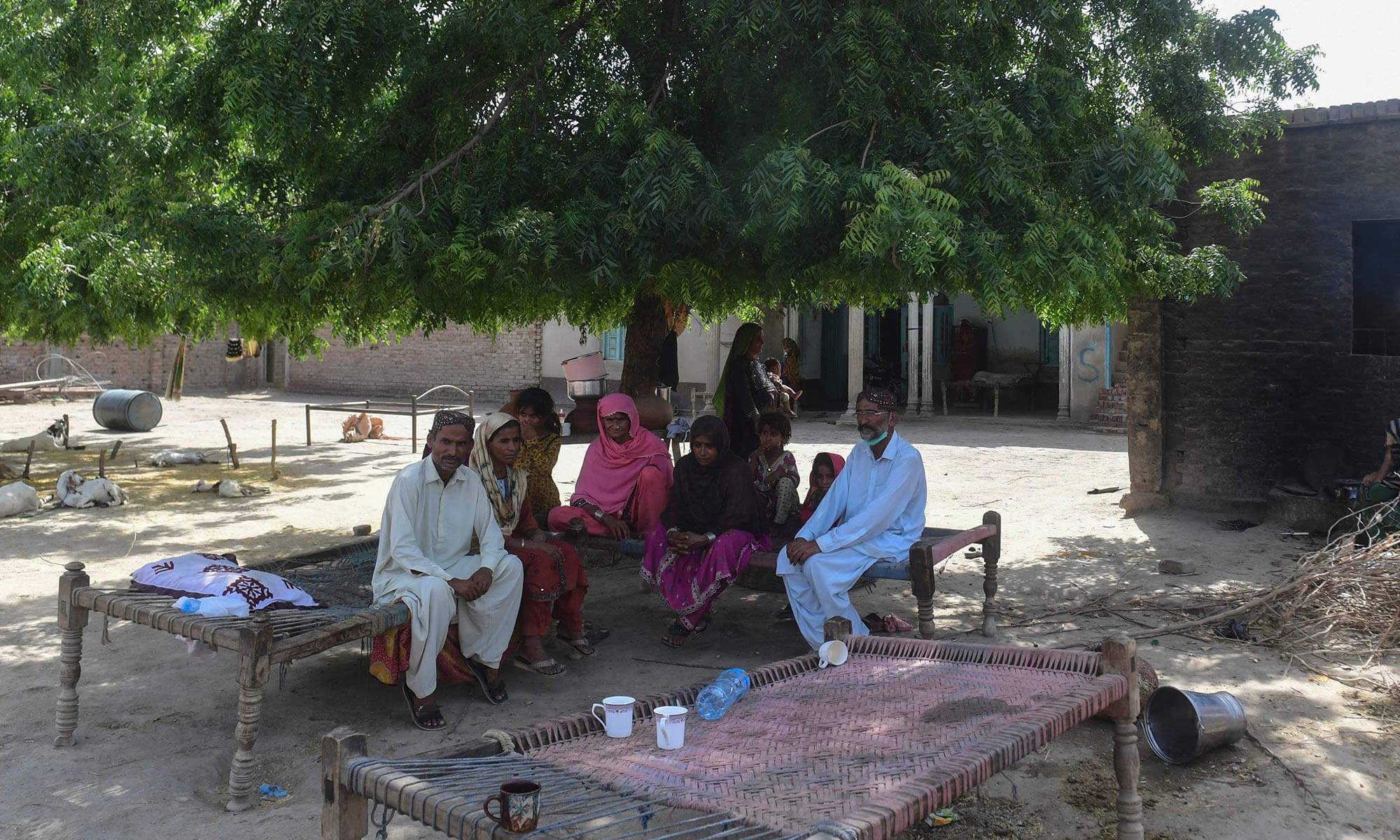 """In this picture taken on June 8, 2021 school teacher Ali Nawaz (R), who helped with the rescue efforts of the train collision, gestures as he sits with his family at his home near the train accident site in Daharki in Sindh Province. - As an express train hurtled through farmland in Pakistan and smashed into the carriages of another service that had derailed minutes earlier, a family of nearby villagers was jolted awake. """"The blast of the collision was so loud that we woke up in panic,"""" said Ali Nawaz, describing the start of a frantic bid to help passengers from the wreckage of the double dis"""