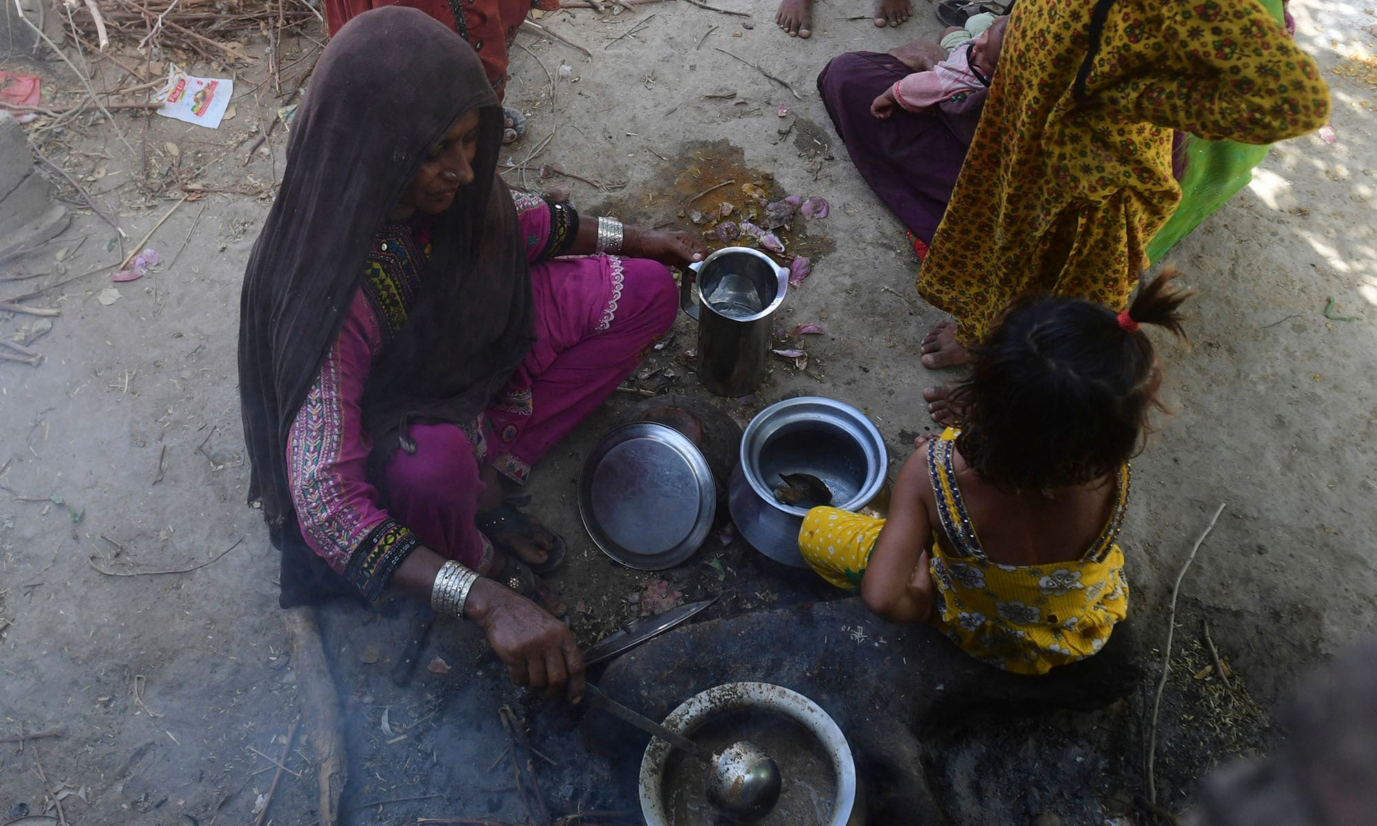 Habiba Mai, wife of Ali Nawaz, a school teacher who helped with the rescue efforts of the train collision, prepares tea for her family at her home near the train accident site in Daharki. — AFP