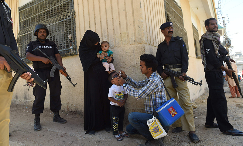 Pakistani policemen stand guard as a health worker administers polio drops to a child during a polio vaccination campaign after a day of an attack by gunmen in Karachi. ─ AFP/File