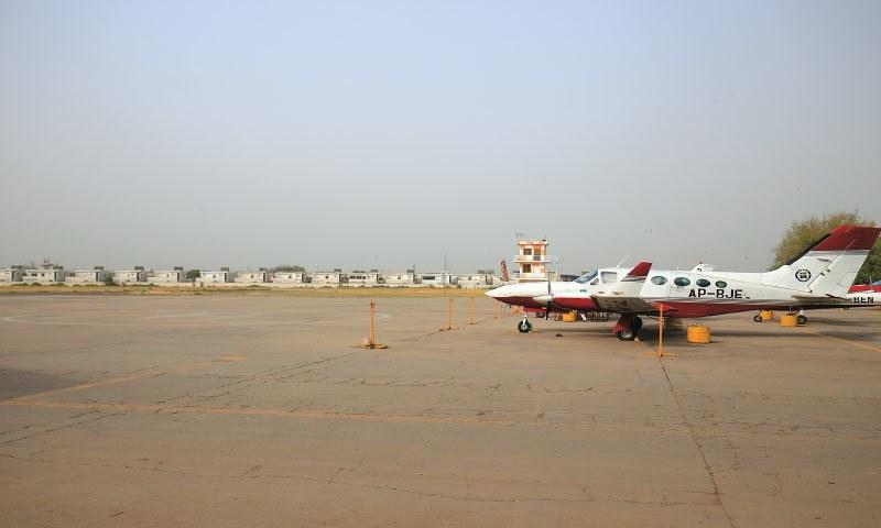 طیارہ، ایئر ٹریفک کنٹرول ٹاور اور اس کے پیچھے پس منظر میں اس زمین پر ایئر فورس رہائش گاہیں بنی ہوئی ہیں جو کبھی فلائنگ کلب کی ملکیت تھی۔