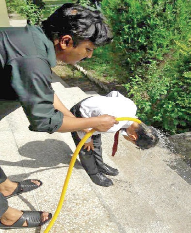 A school staffer pours water on a child at the primary school in Malpur area on Wednesday after several students fainted due to hot weather. — White Star