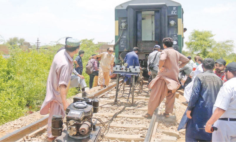 HYDERABAD: Railway employees working to restore a train bogie near Hussainabad on Wednesday. No damage to the bogie of Khyber Mail or injuries to any passenger was reported in the accident.—Online                     Report on Page 15